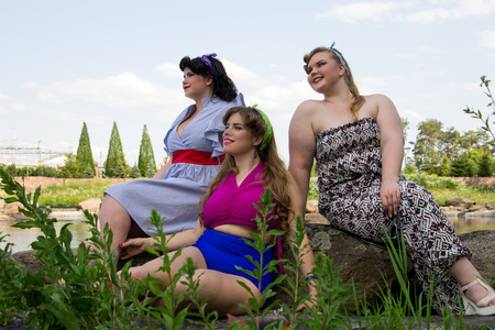 Three Young beautiful plus size models are sitting on a rock , xxl woman portrait near the lake