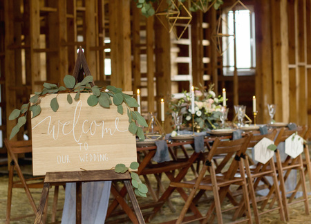 Bord Welkom bij onze bruiloft op de voorgrond. Huwelijksfeest. Vintage-stijl. Stockfoto - 78546823