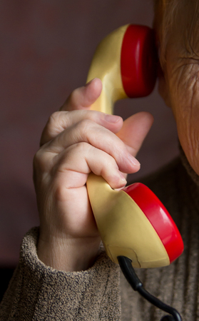 The handset is in the hand of an old woman. ?lose-up view.