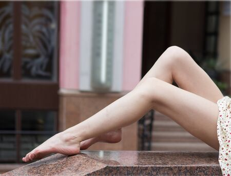 Sexy legs of young girl on a marble parapet. Close up.