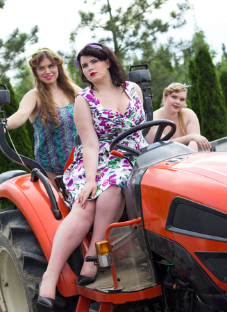 Three beautiful young girls plus size on the tractor in the garden nursery Stock Photo