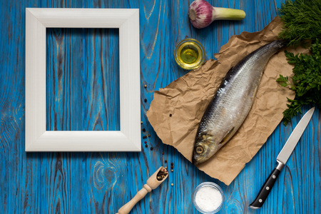 Herring on paper, various spices and herbs on a blue wooden vintage table, white frame with a place for inscription.