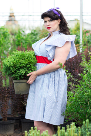 Young beautiful plus size Girl keeps pot with plant  in greenhouse. The girl is working in the garden near the house.