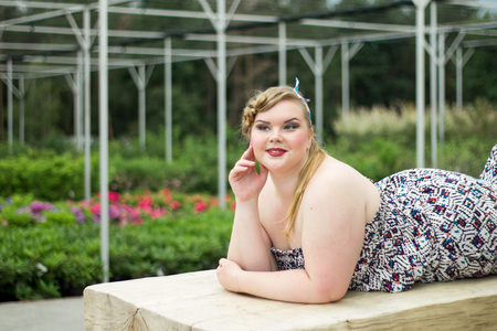 Young beautiful plus size girl is lying on a wooden bench. Girl among the plants in garden. Imagens