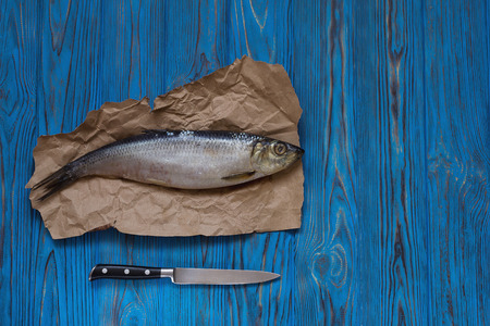 Herring on paper and knife on wooden table. Top view Stockfoto
