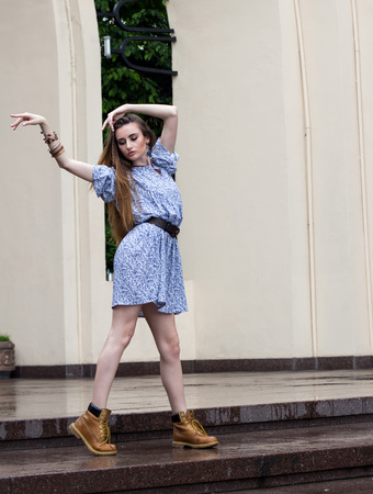 sexy girl dance: girl in a short dress and boots dancing in the city