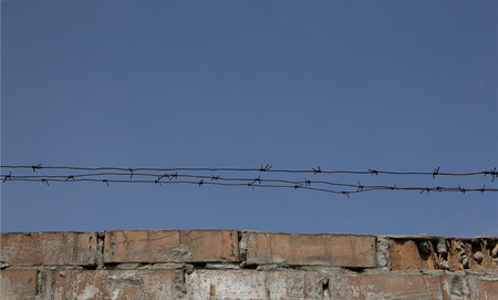 Fencing. Barbed wire over an old brick wall against the sky.