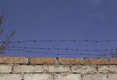 Barbed wire over an old brick wall against the sky. Fencing.