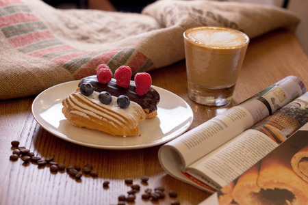 Cappuccino, cake with berries and a journa on table. Closeup.