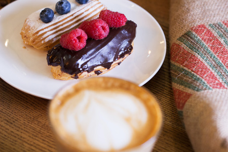 Cappuccino and cake with berries on table. Closeup. Top view. Stock Photo