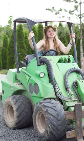 beautiful girl plus size manages a tractor in a garden nursery