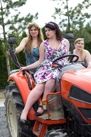 three beautiful girls plus size manages a tractor in a garden nursery Stok Fotoğraf