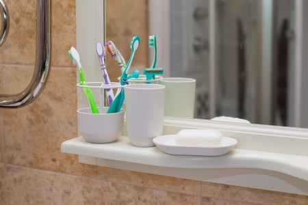 White bath accessories: bar of soap in soap-dish, liquid soap, toothbrushes in the bathroom Фото со стока