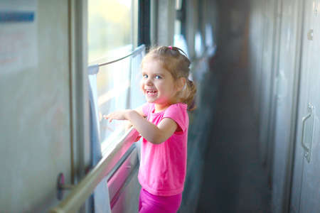 Little baby girl rides the train with her parent on a summer day. Traveling with children. Summer vacation concept Foto de archivo