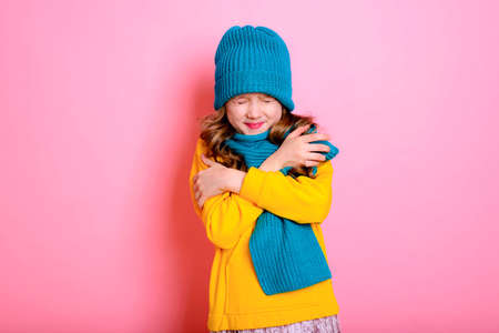 Cold. Virus. Blonde kid child girl is dressed in a warm sweater, scarf, and hat on a pink background. Winter and autumn seasons.
