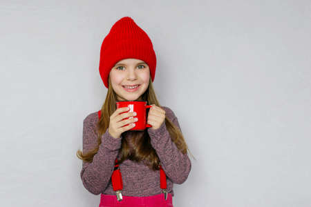 Cute girl in a red hat with a red mug of hot chocolate. Season. Winter holiday. Christmas.