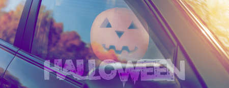 Lettering Halloween. Pumpkin in the car on the driver's seat Harvest pumpkin.