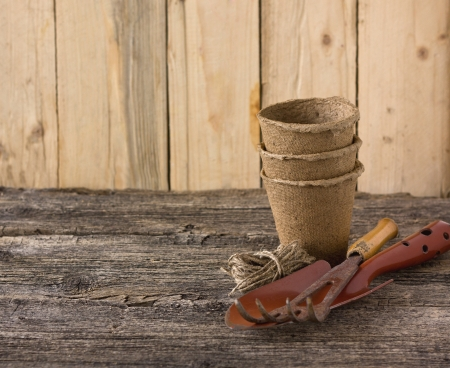 peat pots and garden tools on a wooden board