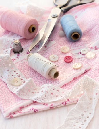 sewing accessories - thread, scissors, needles, buttons, ribbons on the fabric photo