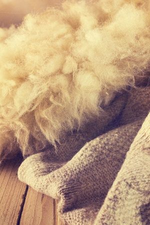 Sheep wool, knitting on a wooden background in vintage style photo