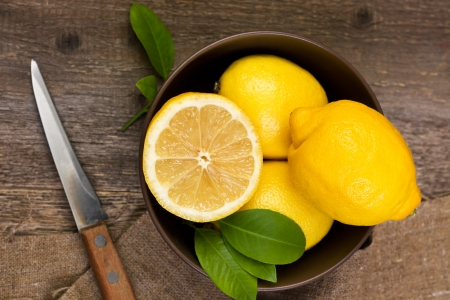 lemons in a bowl on wooden background photo