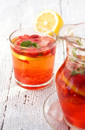 lemonade with strawberries, lemon and ice in a glass on a wooden background