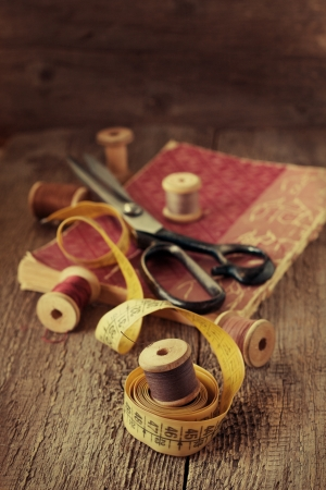 Old spools of thread, measuring tape, scissors on a wooden background photo