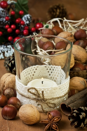 Christmas decoration with candle, nuts and spices on wooden background photo