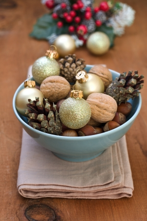 Christmas decoration with nuts, cones, Christmas balls in blue bowl on wooden background photo