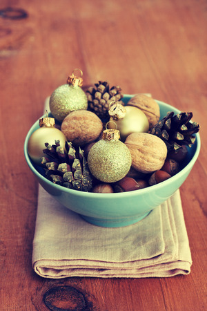 Christmas decoration with nuts, cones, Christmas balls in blue bowl on wooden background (grunge) photo