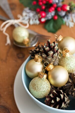 Christmas table setting with golden pine cones and golden Christmas balls photo