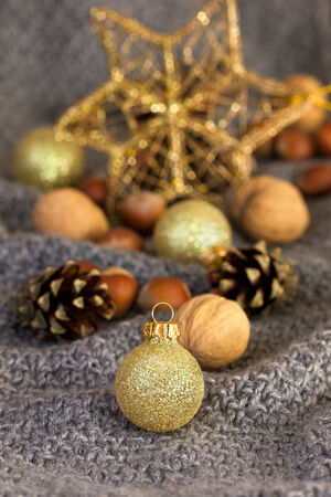 Christmas decorations with Christmas balls, cones and nuts on a knitted background photo