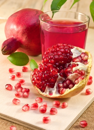 pomegranate juice: a pomegranate, a piece of a pomegranate, a glass of pomegranate juice on a wooden board Stock Photo