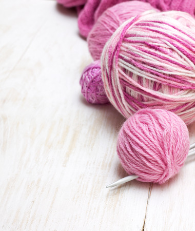 balls of pink yarn on a wooden background
