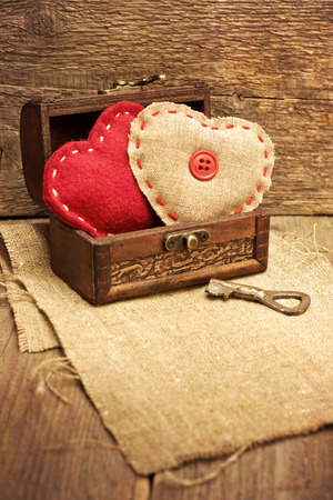 chest with hearts, key on wooden background photo