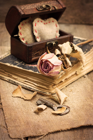 dry rose, old book, chest with hearts, key on wooden background