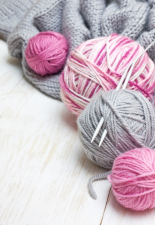 balls of pink and gray yarn, knitted fabric on a wooden background