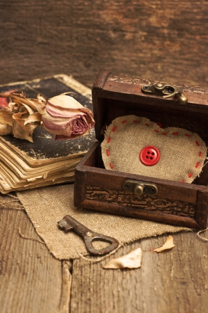 Valentine decorations with chest with hearts, key, dry rose, old book on wooden background (toning, grunge). photo