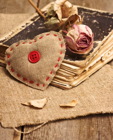 Valentine decorations with heart, dry rose, old book on a wooden background ( toning, grunge). photo