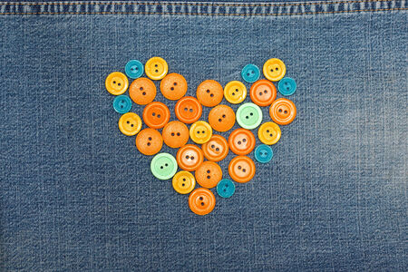 heart from old orange buttons on jeans photo