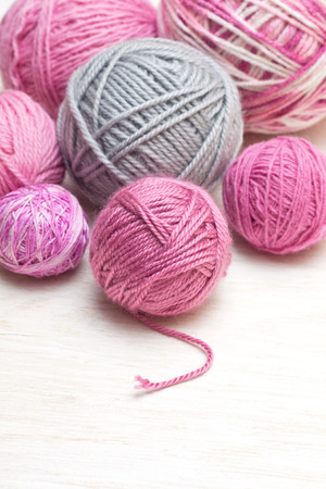 balls of pink and gray yarn on a wooden background Standard-Bild