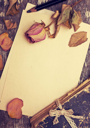 Dry rose and old book on a wooden background 스톡 콘텐츠