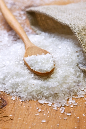 salt and a wooden spoon, sacking on a wooden background 스톡 콘텐츠