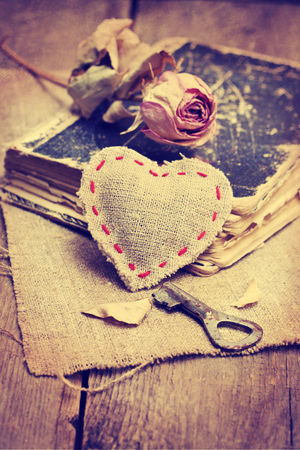 Cloth heart, key, dry rose, old book on a wooden background