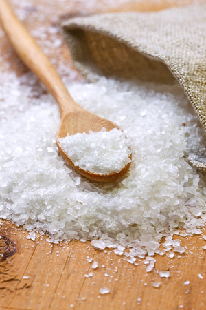 salt and a wooden spoon, sacking on a wooden background photo