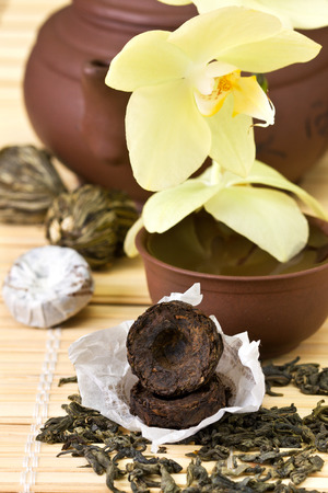 Puer, green tea, ceramic teapot on bamboo background photo