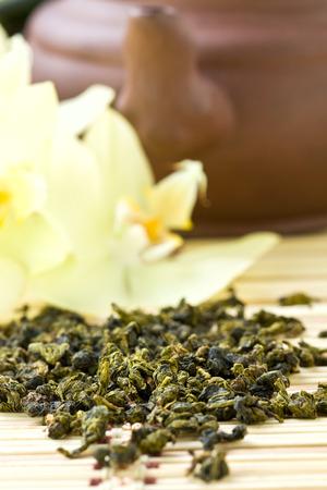 中国緑茶、乾燥枝竹の背景に蘭とセラミック ティーポット
