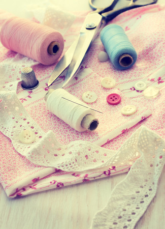 sewing accessories - thread, scissors, needles, buttons, ribbons on the fabric (vintage style) photo