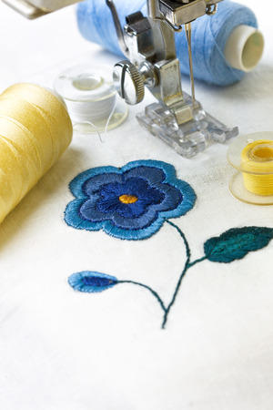 machine embroidery image flower, tools for embroidery: thread, needle, bobbin Standard-Bild