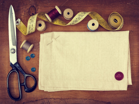 Old spools of thread, fabric, scissors on a wooden background in vintage style